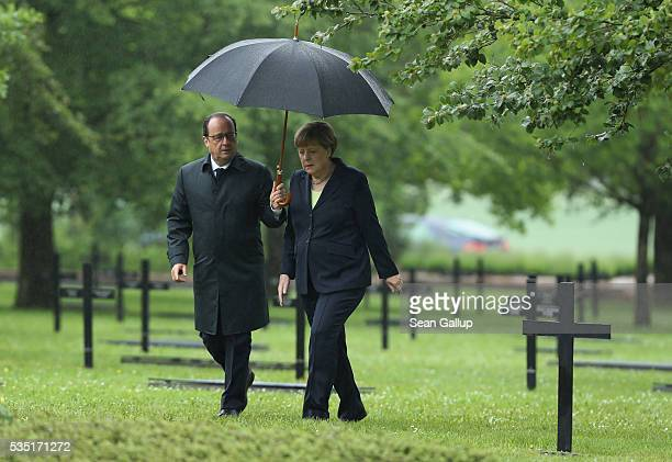 French President Francois Hollande and German Chancellor Angela Merkel arrive to lay a wreath at the German World War I military cemetery at...