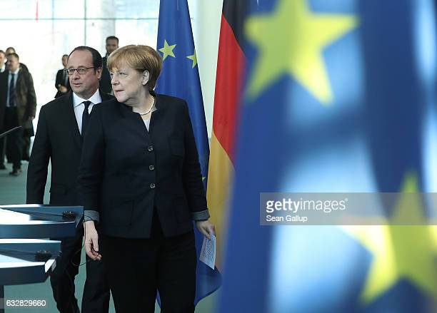 French President Francois Hollande and German Chancellor Angela Merkel arrive to speak to the media prior to talks at the Chancellery on January 27...