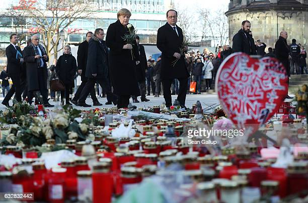 French President Francois Hollande and German Chancellor Angela Merkel arrive to lay flowers at a memorial to the victims of the December Berlin...