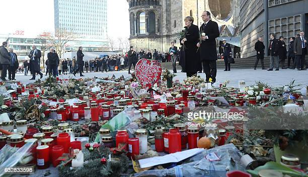 French President Francois Hollande and German Chancellor Angela Merkel prepare to lay flowers at a memorial to the victims of the December Berlin...
