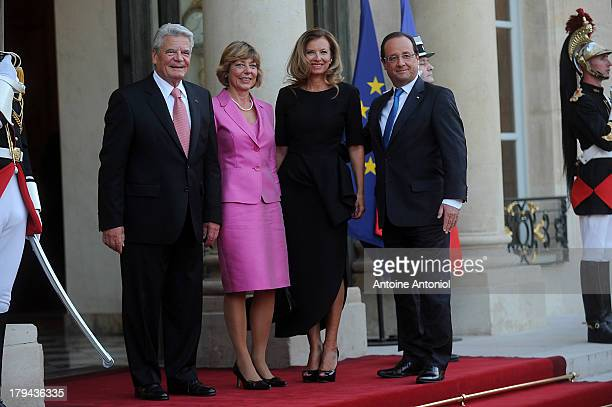 French President Francois Hollande and his companion Valerie Trierweiler pose with the German President's companion Daniela Schadt and the German...
