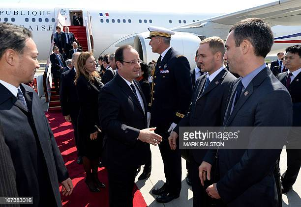 French President Francois Hollande and his partner Valerie Trierweiler greet French officials as they arrive at Capital Airport in Beijing on April...