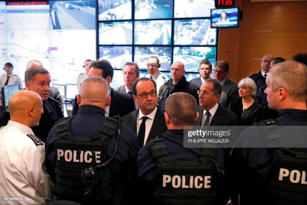 French President Francois Hollande (C) and interim Paris prefect Michel Delpuech (C-R) meet with police officers at the Paris Police headquarters a day after a shooting occurred on the Champs Elysees Avenue in Paris on April 21, 2017. A gunman shot and killed a policeman and wounded two others on the world-famous Champs Elysees avenue in Paris late on April 20, in an attack claimed by the Islamic State group. /