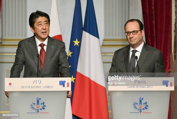French President Francois Hollande and Japanese Prime Minister Shinzo Abe attend a joint press conference in Paris on March 20 2017 During their...