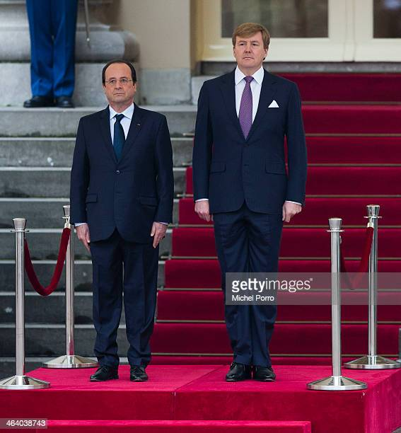 French President Francois Hollande and King Willem-Alexander of The Netherlands listen to the national anthems during the welcome ceremony at the...
