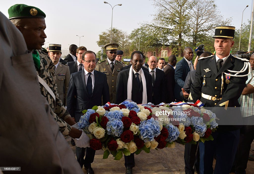 French President Francois Hollande (2ndL) and Malian President Dioncounda Traore (C) lay a wreath at the Independence monument in Bamako on February 2, 2013. Hollande called on Africans to take over the fight against extremism as he received a rapturous welcome today in Mali, where a French-led offensive has driven back Islamist rebels from the north.