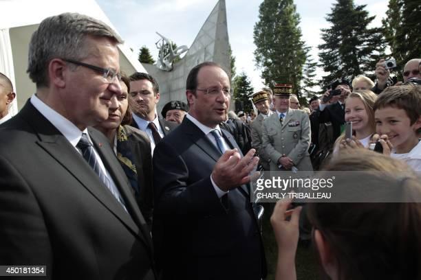 French President Francois Hollande and Poland's President Bronislaw Komorowski salute children during a FrancoPolish ceremony at the polish military...
