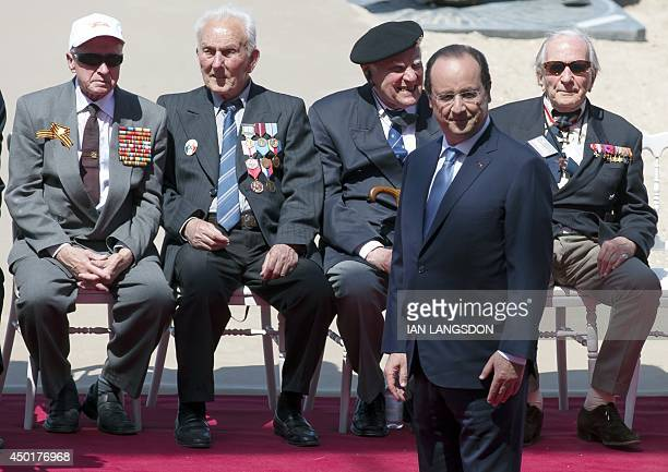 French President Francois Hollande awaits the arrival of foreign dignitaries as WWII veterans sit in the background during an international DDay...