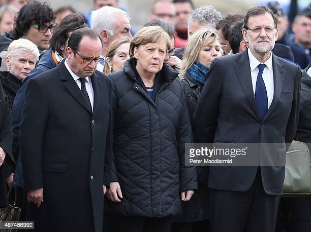 French President Francois Hollande bows his head as he stands with German Chancellor Angela Merkel and Spanish Prime Minister Mariano Rajoy as they...