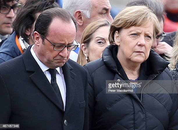 French President Francois Hollande bows his head as he stands with German Chancellor Angela Merkel as they meet with rescue workers on March 25 2015...