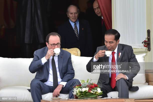 French President Francois Hollande chats with Indonesia's President Joko Widodo as they have a drink during his visit to the presidential palace in...