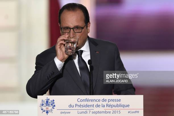 French president Francois Hollande drinks a glass of water during his bi-annual press conference on September 7, 2015 at the Elysee presidential...