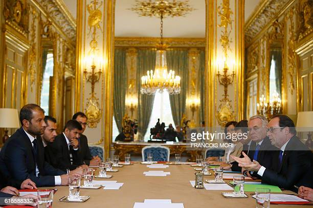 French president Francois Hollande flanked by Foreign Minister JeanMarc Ayrault attend a meeting with Syria's White Helmets leader Raed Saleh with a...