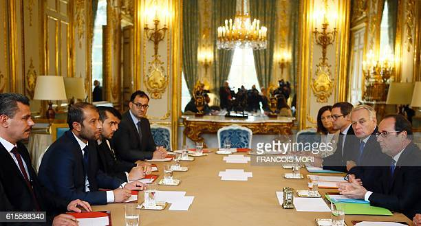 French president Francois Hollande flanked by Foreign Minister JeanMarc Ayrault attend a meeting with Syria's White Helmets leader Raed Saleh and...