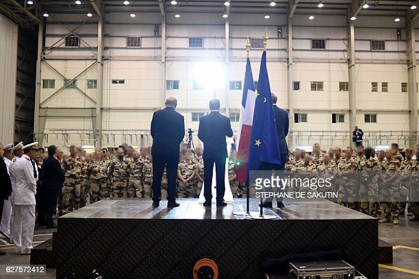 French President Francois Hollande flanked by Foreign Minister JeanMarc Ayrault and Defence Minister JeanYves Le Drian addresses French servicemen...