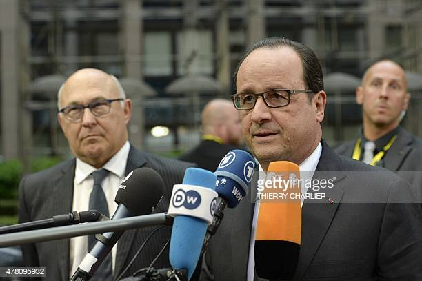 French President Francois Hollande flanked by French Finance Minister Michel Sapin addresses reporters upon his arrival for an emergency Eurogroup...
