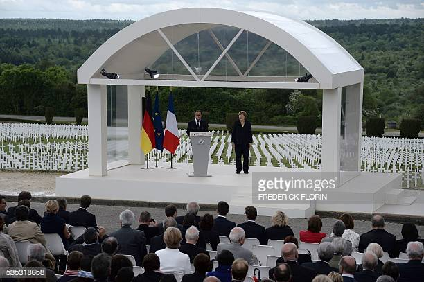 French President Francois Hollande flanked by German Chancellor Angela Merkel delivers a speech at the Douaumont Ossuary northeastern France on May...