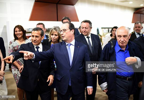 French President Francois Hollande flanked by Peruvian President Ollanta Humala comments on a picture by French photographer Raymond Depardon during...