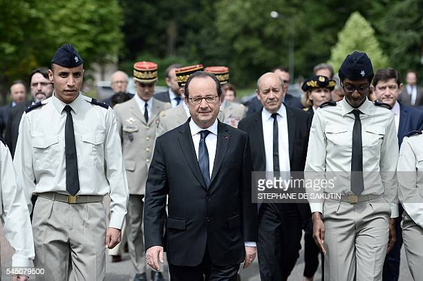 French President Francois Hollande flanked by two of the four military volunteers walks ahead of French defence Minister JeanYves Le Drian as they...