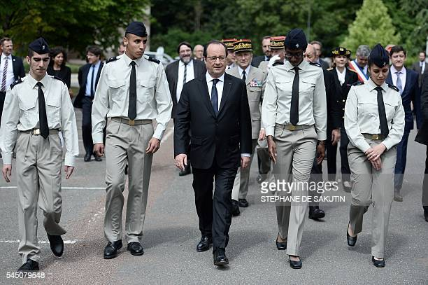French President Francois Hollande flanked the four military volunteers walks ahead of French Army Chief of Staff General Pierre de Villiers as they...