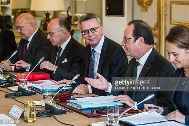 French President Francois Hollande German Interior minister Thomas de Maiziere flanked by French Interior minister Bernard Cazeneuve French minister...