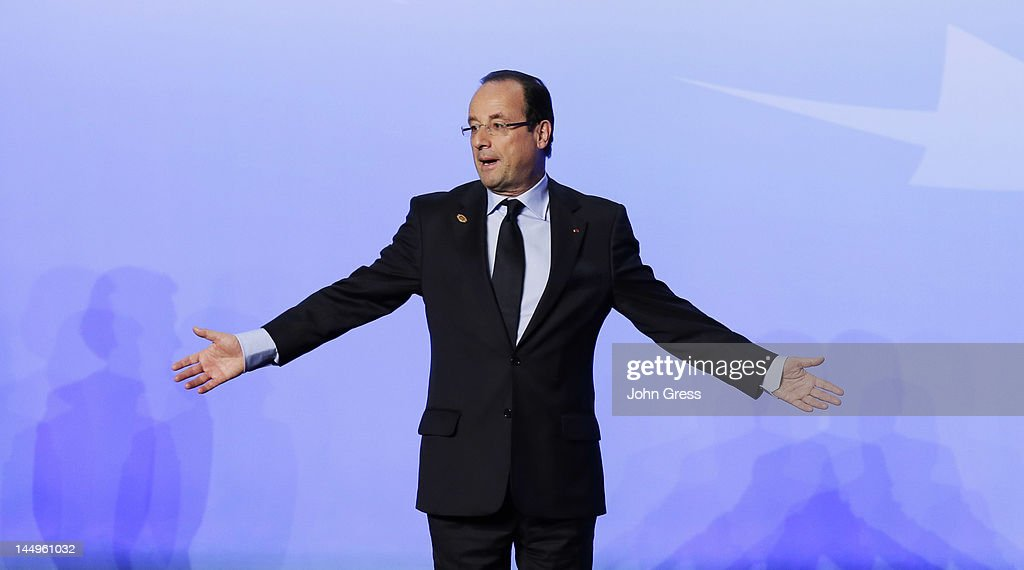 French President Francois Hollande gestures to reporters and photographers after posing for a group photo during the NATO summit on May 21, 2012 at McCormick Place in Chicago, Illinois. As sixty heads of state converge for the two day summit that will address the situation in Afghanistan among other global defense issues, thousands of demonstrators have taken the streets to protest.