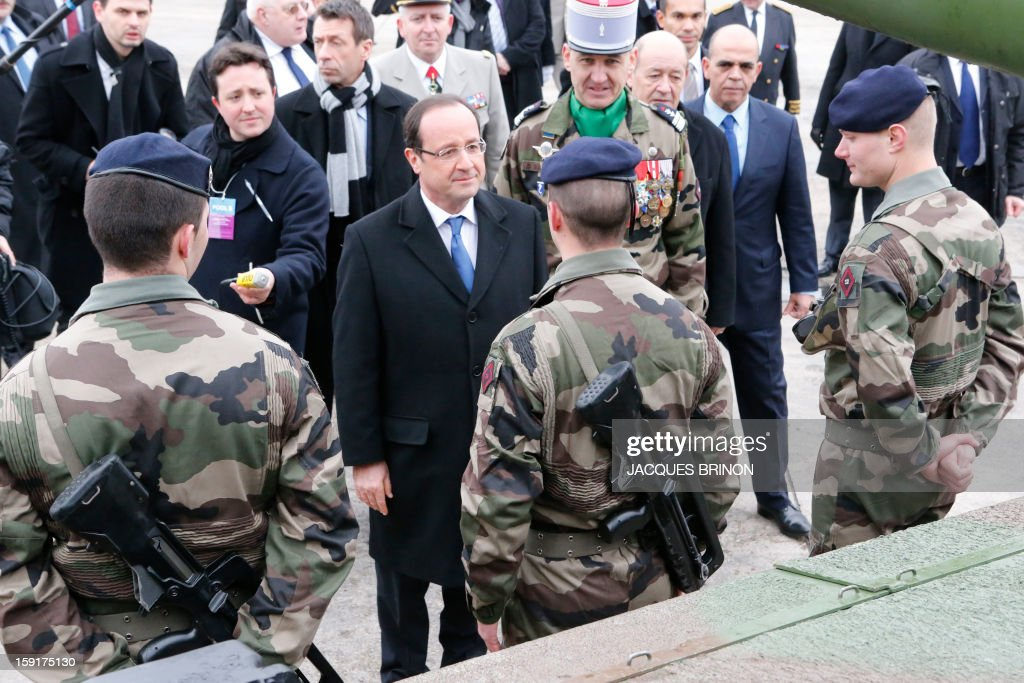 French President Francois Hollande, gets out an armored vehicule of the 12th cuirassiers regiment at the military base of Olivet, central France, as part of a visit to present his New Year's wishes to the French armed forces, on January 9, 2013.