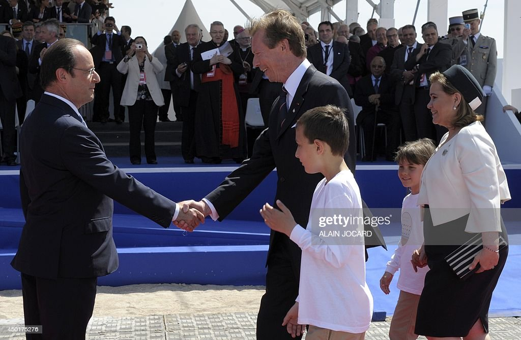 French President Francois Hollande (L) greets Henri, Grand Duke of Luxembourg, and his wife, Maria Teresa, Grand Duchess of Luxembourg, as they arrive for the international D-Day commemoration ceremony in Ouistreham, on June 6, 2014, marking the 70th anniversary of the World War II Allied landings in Normandy.