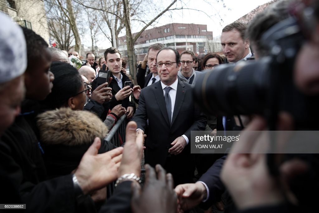 French President Francois Hollande greets the audience upon his arrival for a ceremony to unveil the plaque of a street named after former Aubervilliers' mayor, Jacques Salvator, on March 11, 2017 in Aubervilliers, north of Paris. Jacques Salvator died on March 11, 2016. /
