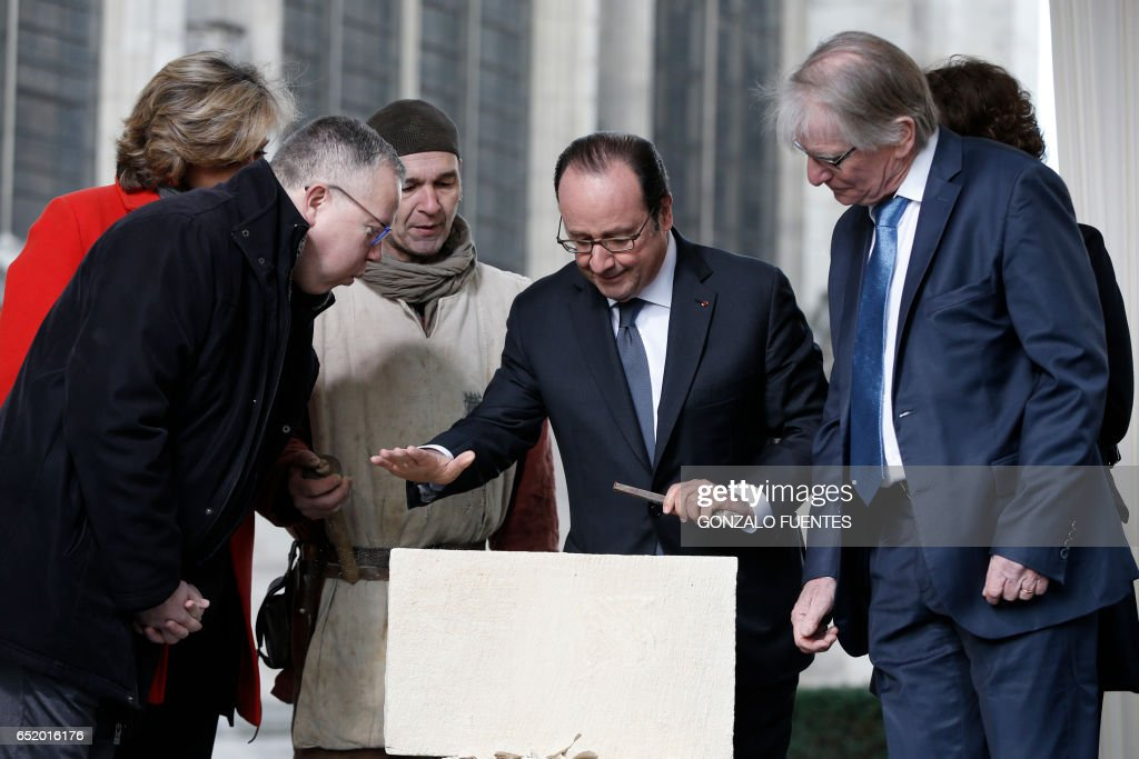 French President Francois Hollande (C) hammers off a stone as Saint Denis Mayor Laurent Russier (L) and French politician Patrick Braouezec (R) stand next to him during an event to lay the first stone of the renovation of the Saint-Denis Basilica in Saint-Denis, near Paris, on March 11, 2017. /