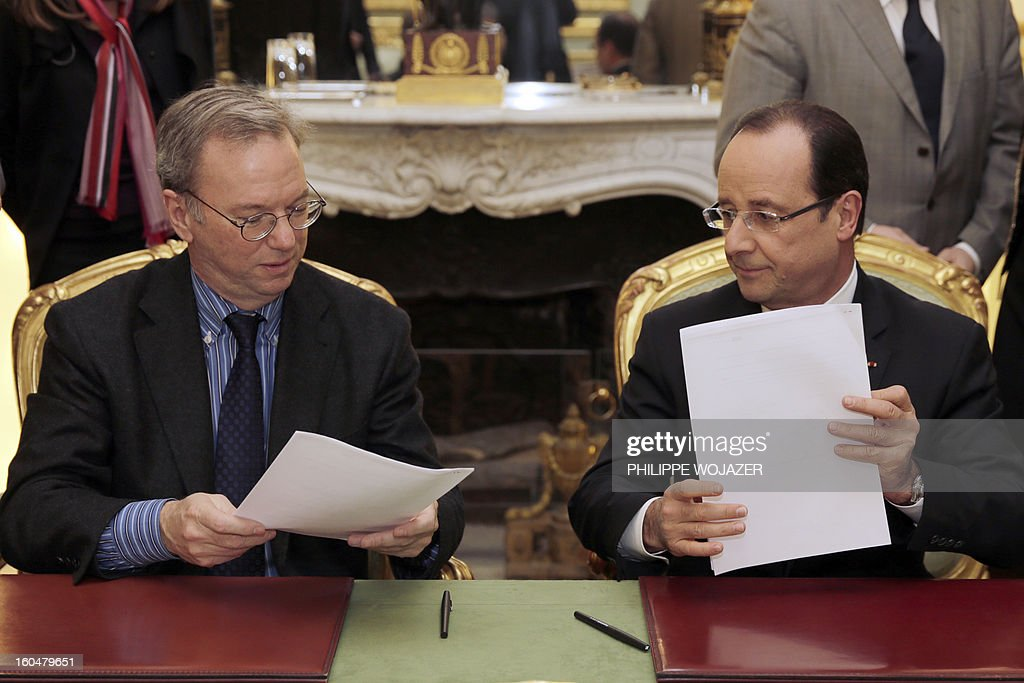 French President Francois Hollande (R) holds documents during a signing agreement meeting with Google Executive Chairman Eric Schmidt at the Elysee Presidential Palace on February 1, 2013 in Paris.