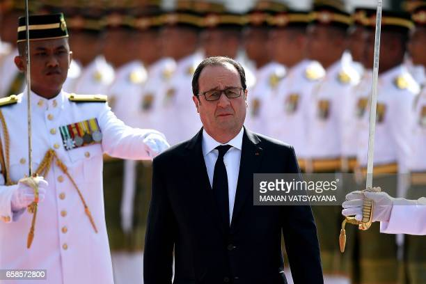French President Francois Hollande inspects a ceremonial guard of honour during a welcoming ceremony at the Parliament House in Kuala Lumpur on March...