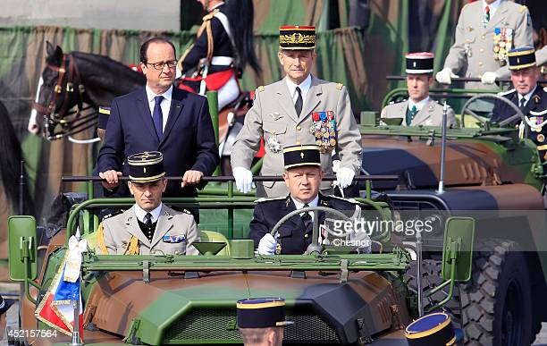 French President Francois Hollande is driven down the ChampsElysees avenue aboard a command car during the annual Bastille Day military parade on...