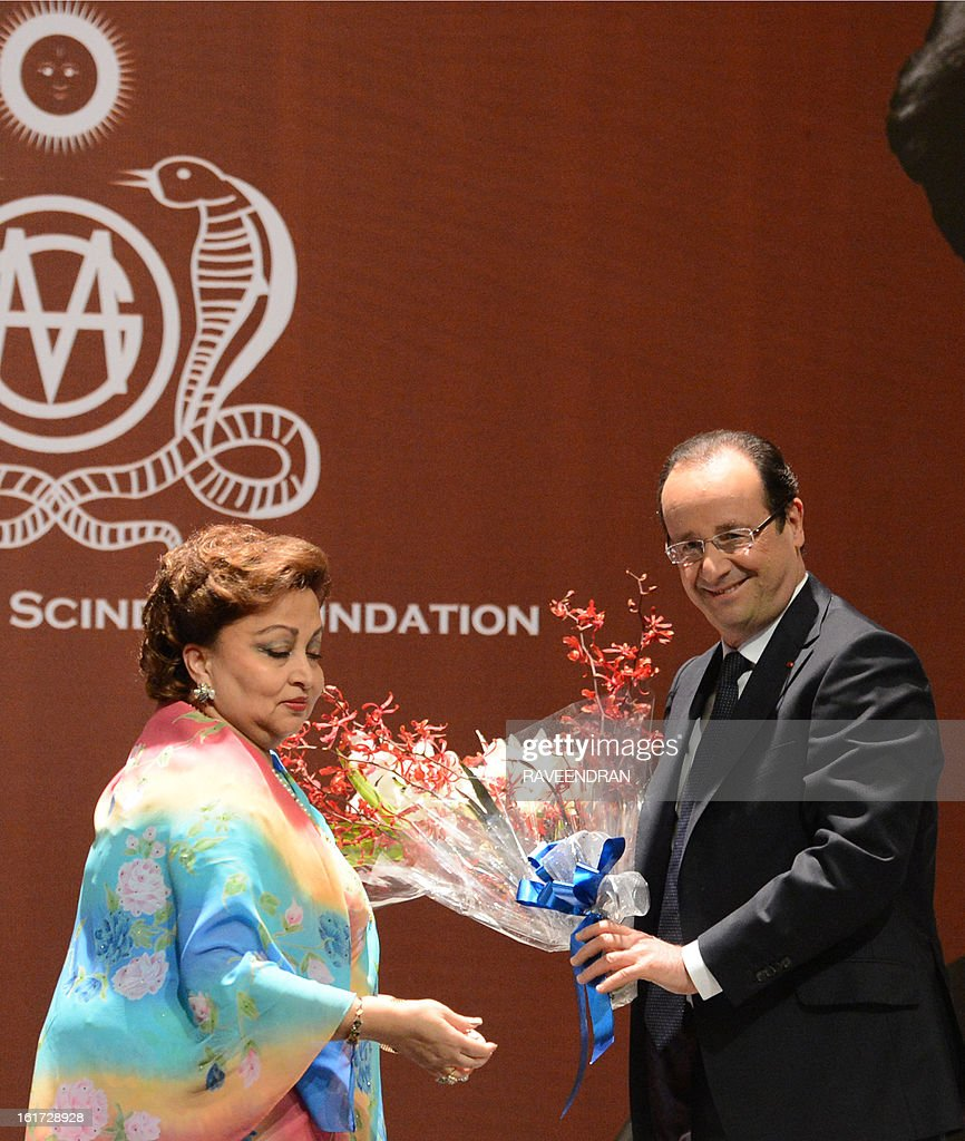 French President Francois Hollande (C) is greeted by Madhavi Raje Scindia (L), wife of the former Minister and Congress leader, Madhavrao Scindia during a Madhavrao Scindia Foundation function in New Delhi on February 15, 2013. French President Francois Hollande in India for a two-day visit.