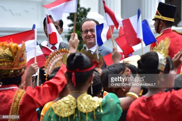 French President Francois Hollande is greeted by people waving French and Indonesian flags during his visit to the presidential palace in Jakarta on...