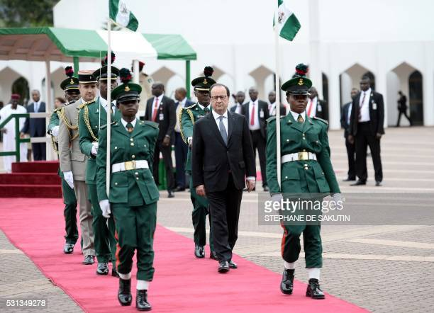 TOPSHOT French President Francois Hollande is pictured during a welcoming ceremony prior to a meeting with Nigerian president at the presidential...
