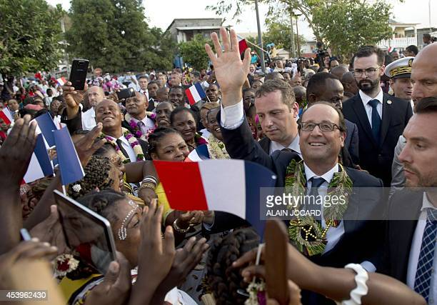 French President Francois Hollande is welcomed by wellwishers upon his arrival in Dzaoudzi on August 22 as part of a visit to the French overseas...