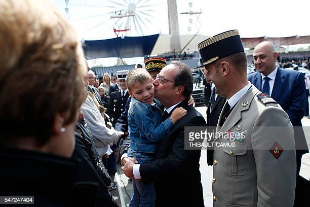 French President Francois Hollande kisses a child on the ChampsElysees avenue after the Bastille Day Parade in Paris July 14 2016 France holds annual...