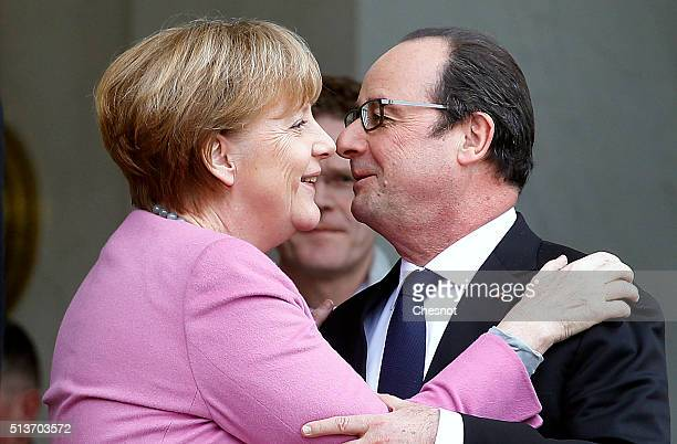 French President Francois Hollande kisses with German Chancellor Angela Merkel after their meeting at the Elysee palace on March 04, 2016 in Paris....