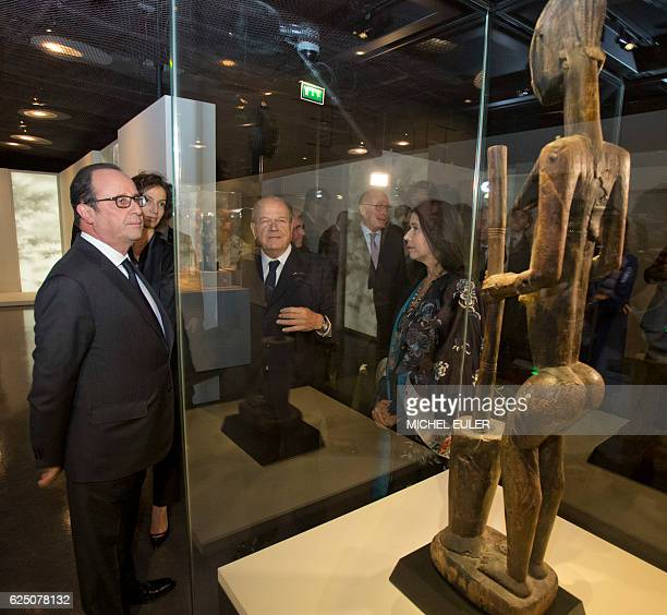 French President Francois Hollande looks at a 17th18th century woman statue using a pestle and a mortar of Dogon N'duleri style and from Mali during...