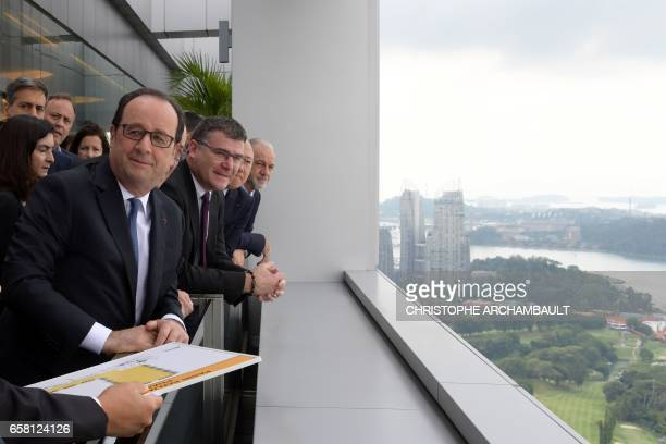 French President Francois Hollande looks at the view during a visit to the Pasir Panjang Terminal in Singapore on March 27 2017 Hollande is in...