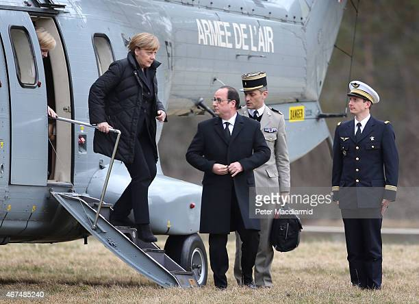 French President Francois Hollande looks round as German Chancellor Angela Merkel walks down the steps of a military helicopter as they arrive to...