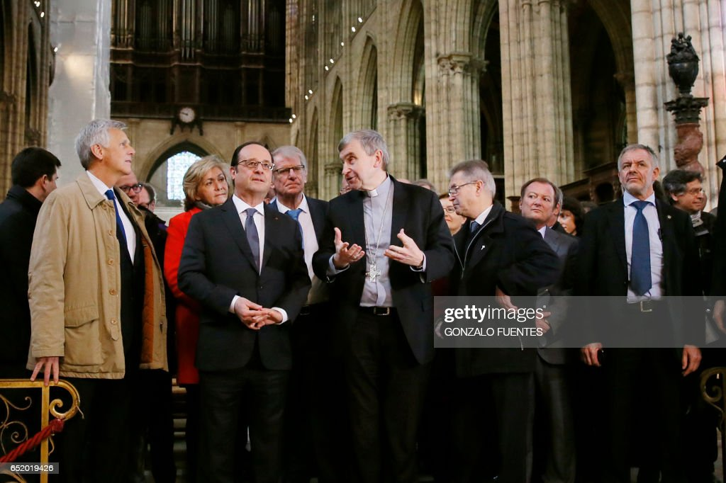 French President Francois Hollande (C, left), next to French architect Jacques Moulin (L), listens to Bishop of Saint-Denis Pascal Delannoy (C, right) during an event to lay the first stone of the renovation of the Saint-Denis Basilica in Saint-Denis, near Paris, on March 11, 2017. /