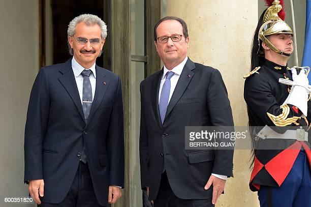 French President Francois Hollande poses for a photograph as he welcomes Saudi Prince Al Waleed bin Talal bin Abdulaziz Al Saoud at the Elysee...