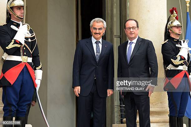 French President Francois Hollande poses for a photograph as he welcomes Saudi Prince Al Waleed bin Talal bin Abdulaziz Al Saoud at the Elysee...