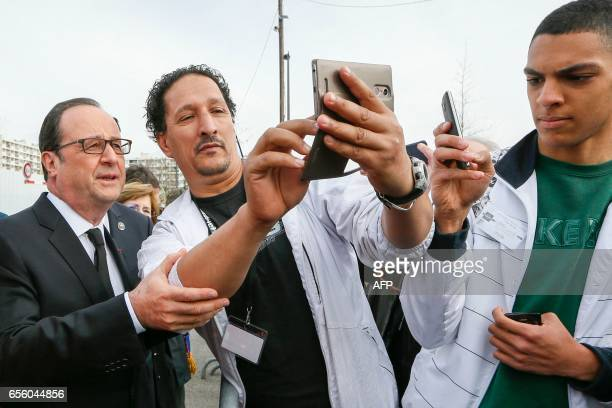 French President Francois Hollande poses for a selfie during a visit in Vaulx-en-Velin, near Lyon, on March 21, 2017. / AFP PHOTO / POOL / ROBERT...