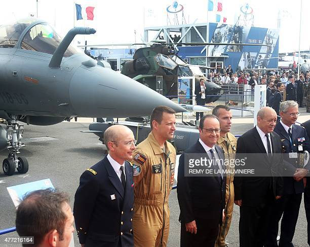 French President Francois Hollande poses in front of a French Rafale jet fighter with French defense minister JeanYves Le Drian during the...