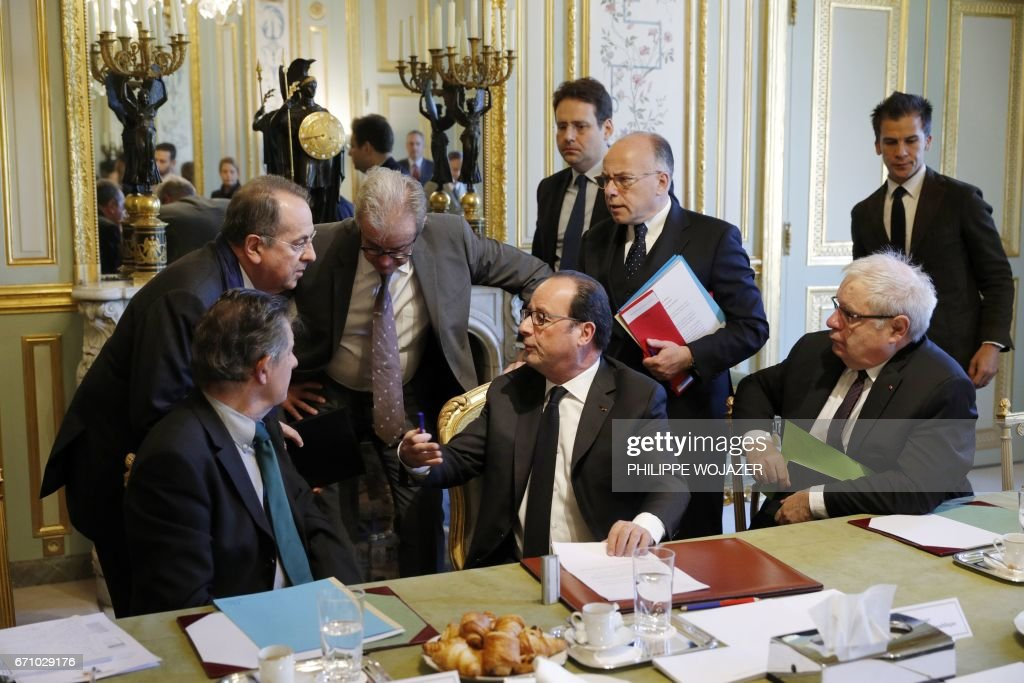 French President Francois Hollande (C), President's Chief of Staff, Jean-Pierre Jouyet (L), Interior Minister Matthias Fekl (Rear C), Prime Minister Bernard Cazeneuve (C-R), head of Hollande's communication service Gaspard Gantzer (R) and French Justice Minister, Jean-Jacques Urvoas (Rear L) attend a meeting of the Defense Council on April 21, 2017 at the Elysee Palace in Paris, after a gunman opened fire on police on the Champs Elysees a day before. A gunman shot and killed a policeman and wounded two others on the world-famous Champs Elysees avenue in Paris on April 20 in an attack claimed by the Islamic State group. /
