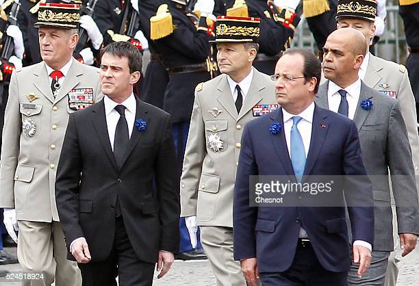 French President Francois Hollande ©, Prime Minister Manuel Valls and Junior Minister for Veterans Kader Arif review troops as they arrive at the Arc...