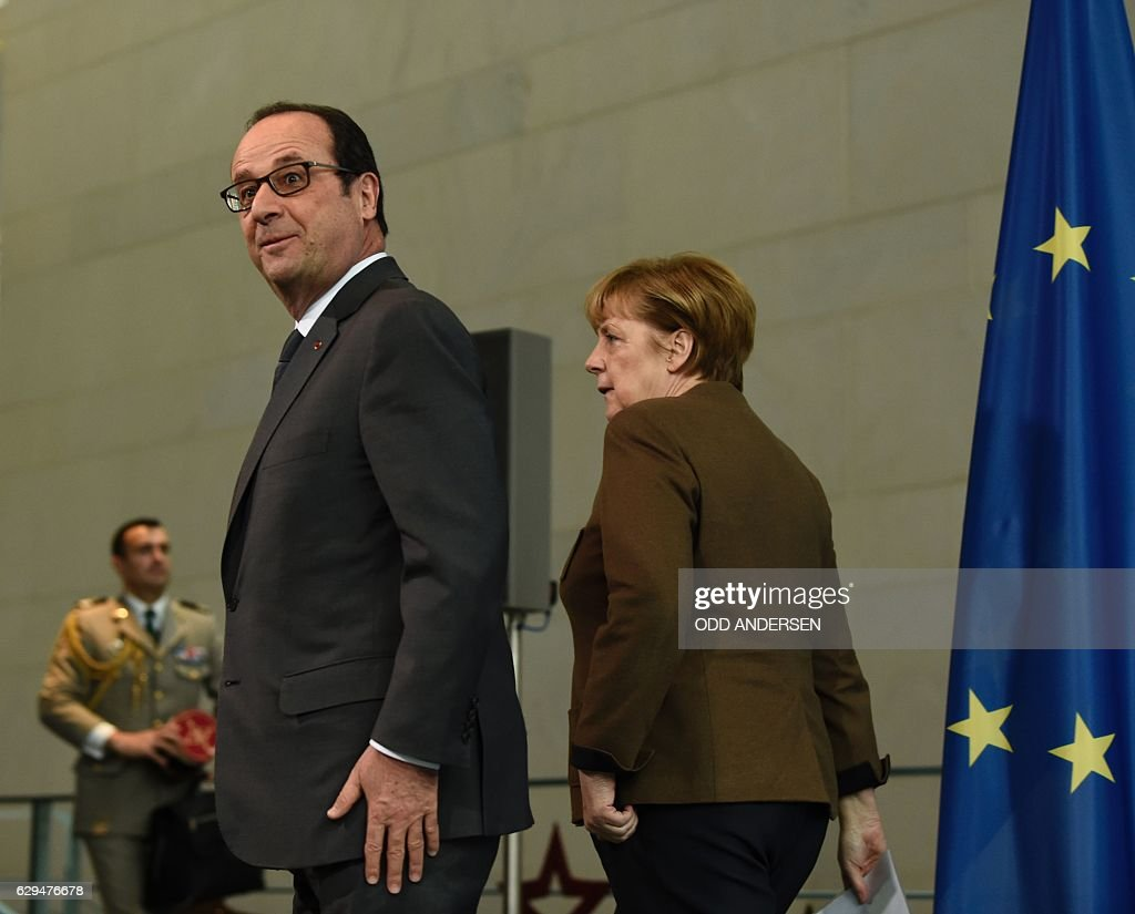 French President Francois Hollande (L) reacts after a joint press conference with German chancellor Angela Merkel at the Chancellery in Berlin on December 13, 2016. / AFP / ODD
